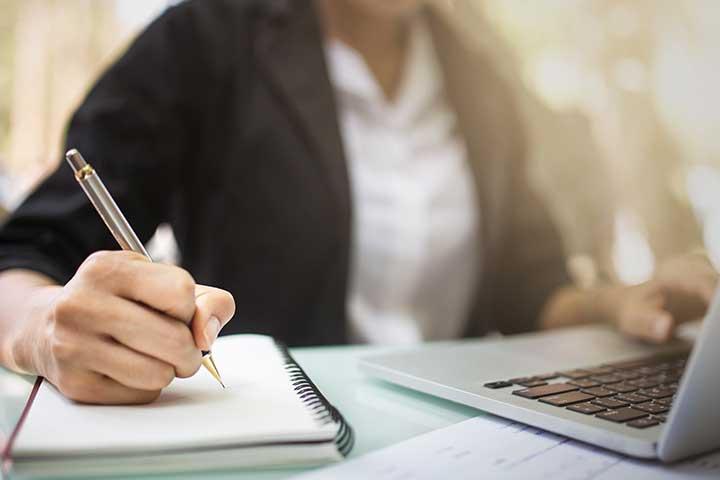 Mulher sentada em frente ao computador, com foco em sua mão direita, escrevendo em um caderno